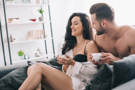 Foto de Hombre guapo y mujer atractiva en el sostén sosteniendo tazas y sonriendo - Imagen libre de derechos