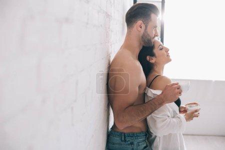Photo pour Vue de côté de l'homme beau et des tasses sexy de fixation de femme - image libre de droit