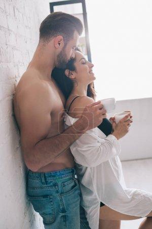 Photo pour Vue de côté de l'homme beau et des tasses sexy de fixation de femme près du mur - image libre de droit
