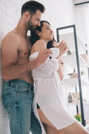 Photo for Low angle view of handsome man and sexy woman with closed eyes in bra holding cups - Royalty Free Image