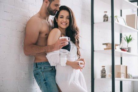 Photo pour Homme beau et femme de sourire dans des tasses de fixation de chemise - image libre de droit