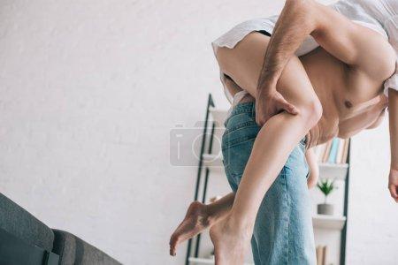 Foto de Vista recortada del hombre en jeans y mujer sexy en la camisa jugando - Imagen libre de derechos