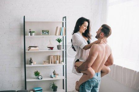 Photo pour Homme musculaire dans la fixation et étreignant de jeans avec la femme sexy dans la chemise - image libre de droit