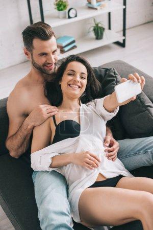 Foto de Hombre guapo y mujer sexy en camisa y sujetador sonriendo y tomando selfie - Imagen libre de derechos