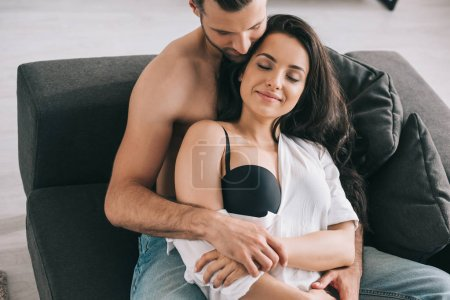 Photo for Handsome man and sexy woman with closed eyes in shirt hugging - Royalty Free Image