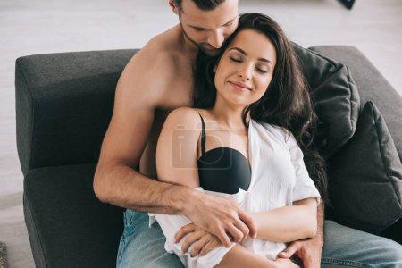 Foto de Hombre guapo y mujer sexy con los ojos cerrados en la camisa abrazándose - Imagen libre de derechos