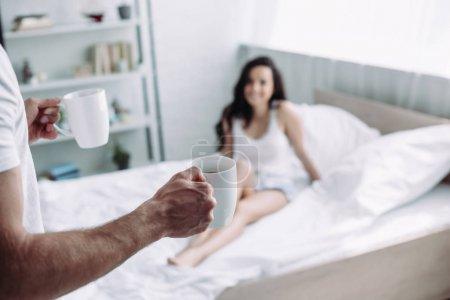 Photo pour Foyer sélectif des tasses de fixation d'homme avec le thé et la femme s'asseyant sur le lit - image libre de droit