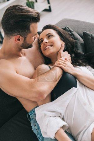 Photo pour Homme beau et femme sexy dans la chemise se trouvant sur le sofa et étreignant - image libre de droit
