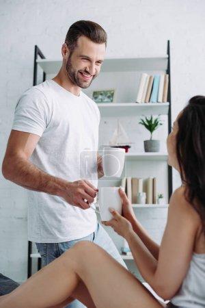 Photo pour Homme beau et souriant donnant la tasse avec le thé à la femme brune - image libre de droit