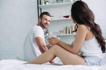 Foto de Hombre guapo y sonriente hablando con la mujer morena en el apartamento - Imagen libre de derechos