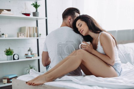 Photo for Attractive and brunette woman with closed eyes lying on shoulder of boyfriend - Royalty Free Image