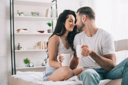 attractive and brunette woman with closed eyes and man with cups kissing