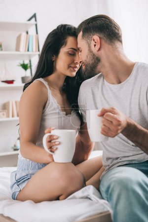 Photo for Attractive and brunette woman with closed eyes and man with cups kissing - Royalty Free Image