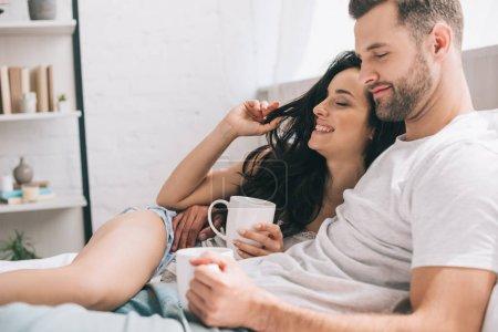 Photo pour Femme attirante et brunette retenant des tasses, se trouvant sur le lit et étreignant - image libre de droit