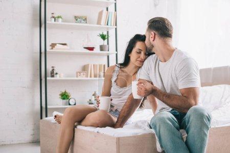 Photo pour Homme dans la tasse de fixation de t-shirt et embrassant la femme attirante et sexy - image libre de droit