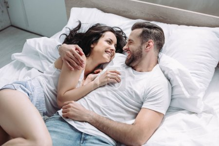 Photo for Attractive and brunette woman and man smiling, lying on bed and hugging - Royalty Free Image