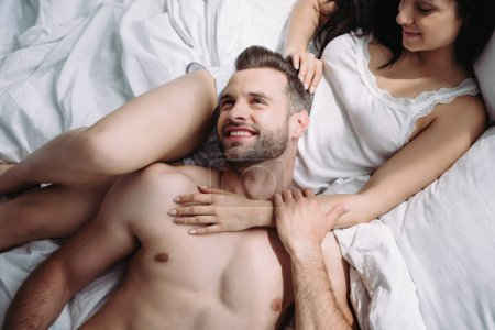 Photo for Top view of handsome and shirtless man lying on attractive woman - Royalty Free Image