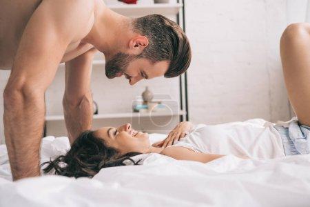 Photo pour Vue de côté de l'homme beau regardant la femme se trouvant sur le lit - image libre de droit