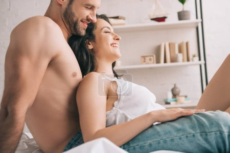 Photo for Side view of attractive woman with closed eyes and handsome man smiling in bedroom - Royalty Free Image