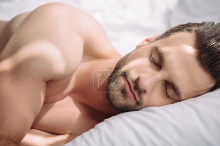 Photo pour Homme beau et torse nu avec les yeux fermés dormant dans le lit - image libre de droit