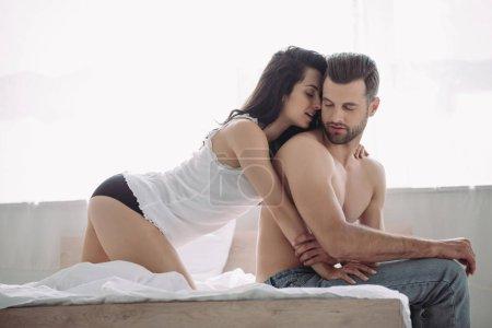 Foto de Hermosa y morena mujer abrazando hombre guapo en jeans - Imagen libre de derechos