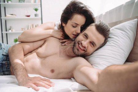 Photo pour Foyer sélectif de la belle femme et bel homme prenant le selfie dans la chambre à coucher - image libre de droit