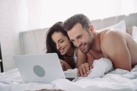 Foto de Hermosa mujer y hombre guapo acostado en la cama y el uso de la computadora portátil - Imagen libre de derechos