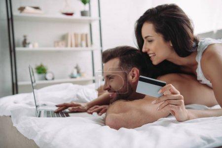 Photo pour Belle femme retenant la carte de crédit et l'homme beau utilisant l'ordinateur portatif - image libre de droit
