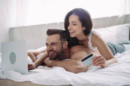 Foto de Hermosa y sonriente mujer sosteniendo tarjeta de crédito y hombre guapo usando portátil - Imagen libre de derechos