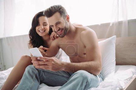 Photo pour Homme beau et souriant retenant le smartphone et la femme pointant avec le doigt à lui - image libre de droit