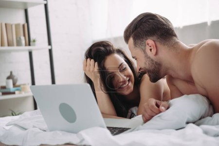 Foto de Beautiful woman and handsome man lying on bed with laptop - Imagen libre de derechos