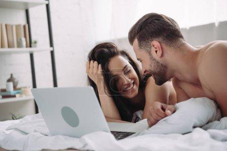 Photo pour Belle femme et bebeau homme se trouvant sur le lit avec l'ordinateur portatif - image libre de droit