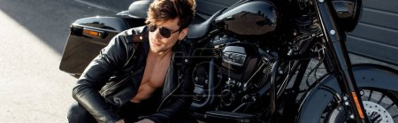 Photo for Panoramic shot of young man in glasses and leather jacket sitting near motorcycle - Royalty Free Image