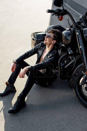 Photo pour Jeune homme s'asseyant sur le sol près de la moto, souriant et regardant loin - image libre de droit