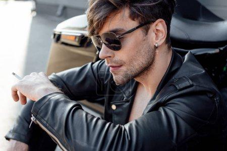 Photo pour Jeune motocycliste dans la veste en cuir fumant tout en s'asseyant près de la moto - image libre de droit