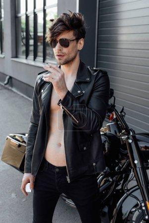 Photo pour Jeune motocycliste avec le torse nu musculaire restant près du tabagisme noir de moto et retenant le briquet - image libre de droit