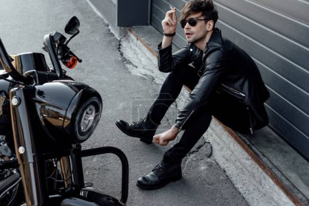 Photo for Handsome motorcyclist in sunglasses sitting on ground near motorcycle and smoking cigarette - Royalty Free Image