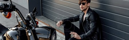 Photo for Panoramic shot of handsome motorcyclist in sunglasses sitting on ground near motorcycle and holding cigarette - Royalty Free Image