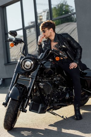 Photo pour Handsome man in sunglasses all in black clothes sitting on motorcycle and looking away - image libre de droit