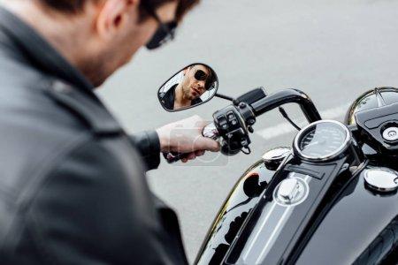 Photo pour Foyer sélectif de la réflexion du jeune homme dans les gasses de soleil s'asseyant sur la moto - image libre de droit