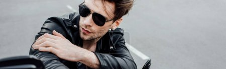 Photo for Panoramic shot of cool man in sunglasses sitting on motorcycle and looking away - Royalty Free Image