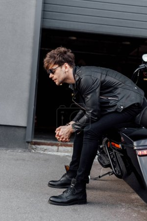 Photo for Side view of handsome man in leather jacket sitting on black motorcycle - Royalty Free Image