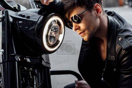 Photo pour Beau jeune homme appuyé sur la lampe lumineuse sur la moto - image libre de droit