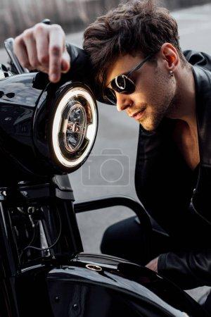 Photo pour Beau jeune homme en lunettes de soleil appuyé sur la lampe lumineuse sur la moto - image libre de droit