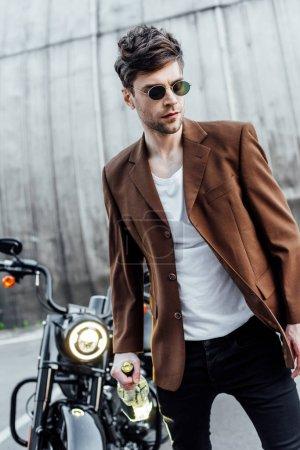 Photo pour Foyer sélectif de bel homme en lunettes de soleil et veste brune marche avec bouteille d'alcool près de la moto - image libre de droit