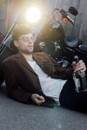 Photo pour Jeune homme couché sur le sol près de la moto avec lampe lumineuse - image libre de droit