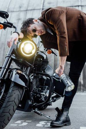 Photo pour Jeune homme penché tête sur le guidon de la moto avec lampe lumineuse tout en tenant bouteille avec de l'alcool - image libre de droit