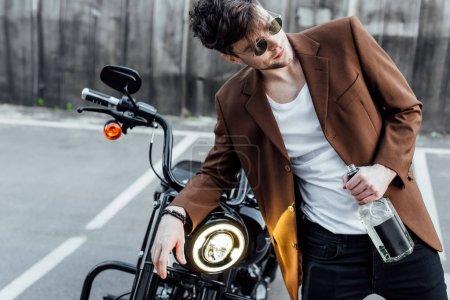 Photo pour Bel homme en costume appuyé sur le guidon avec lampe lumineuse, tenant la bouteille avec de l'alcool et loking loin - image libre de droit