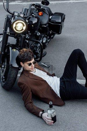 Photo pour Beau jeune homme en lunettes de soleil couché sur le sol près de la moto avec lampe lumineuse - image libre de droit