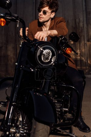 Photo pour Vue avant de l'homme dans des lunettes de soleil s'asseyant sur la moto et regardant loin - image libre de droit